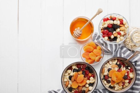 top view of bowls with muesli, dried berries and nuts served for breakfast with dried apricots and honey on white wooden table