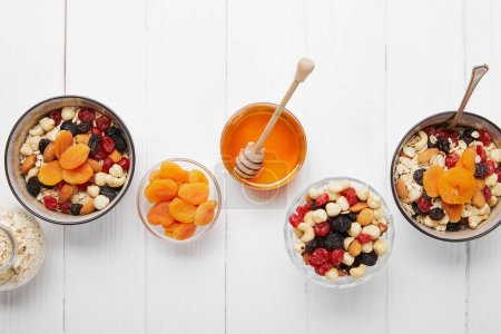 Photo for Top view of bowls with cereal, dried apricots and berries, honey and nuts served for breakfast on white wooden table - Royalty Free Image