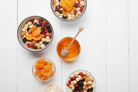 top view of bowls with cereal, dried apricots and berries, honey and nuts on white wooden table