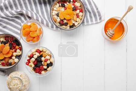 Photo for Top view of bowls with cereal, dried apricots and berries, honey and nuts on white table with striped napkin - Royalty Free Image
