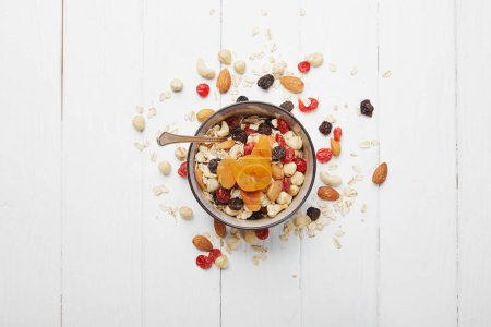 top view of bowl full of muesli with dried apricots, berries and scattered nuts around on white wooden table