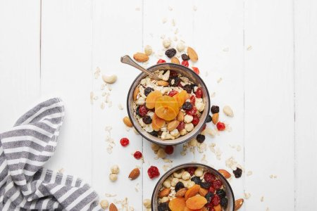 Photo for Top view of bowls with muesli, dried apricots and berries and nuts served for breakfast with scattered ingredients on white wooden table - Royalty Free Image