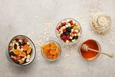 Photo for Top view of bowls with muesli, dried apricots and berries, nuts and honey on textured grey surface with messy scattered oat flakes - Royalty Free Image
