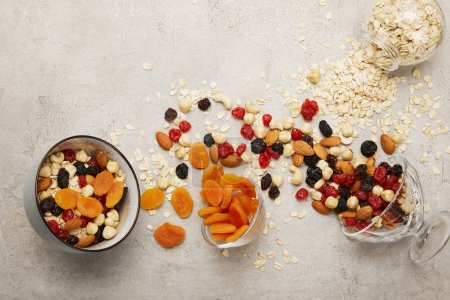 Photo for Top view of bowls with muesli, dried apricots and berries, nuts on textured grey surface with messy scattered ingredients - Royalty Free Image