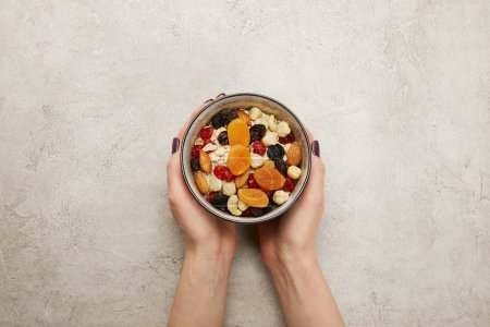 Photo for Cropped view of woman holding bowl with muesli, dried apricots and berries, nuts on textured grey surface - Royalty Free Image