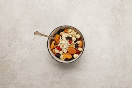 Photo for Top view of bowl with muesli, dried apricots and berries, nuts and spoon on textured grey surface - Royalty Free Image