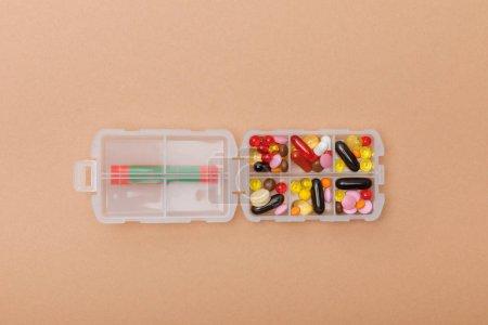 Photo pour Vue de dessus de récipient avec des pilules colorées sur la surface brune - image libre de droit