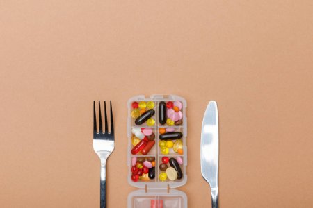 Photo for Top view of container with pills and cutlery on brown surface - Royalty Free Image