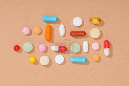 Photo pour Vue du dessus des pilules colorées sur la surface brune - image libre de droit