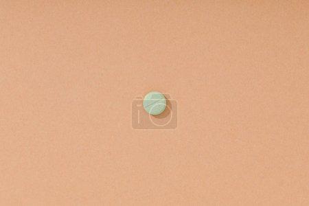 Foto de Vista superior de la píldora verde en la superficie marrón - Imagen libre de derechos