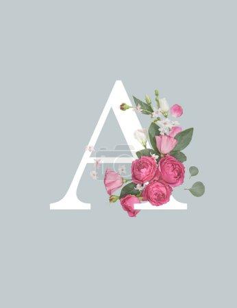 Photo pour Lettre blanche A avec des fleurs d'Eustoma rose et des feuilles vertes isolées sur le gris - image libre de droit