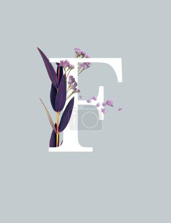 Photo pour Lettre blanche F avec fleurs sauvages violettes et feuilles isolées sur le gris - image libre de droit