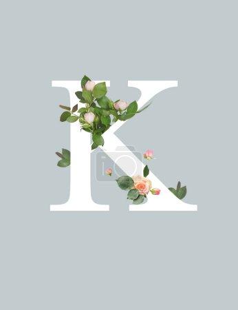 Photo pour Lettre blanche K avec des roses et des feuilles vertes isolées sur le gris - image libre de droit