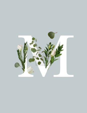 Photo pour Lettre blanche M avec des fleurs et des feuilles vertes isolées sur le gris - image libre de droit