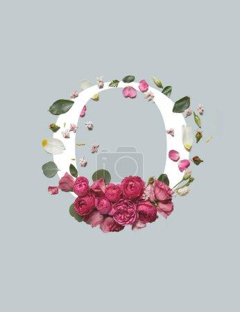 Photo pour Lettre blanche O avec fleurs d'Eustoma rose et feuilles vertes isolées sur le gris - image libre de droit