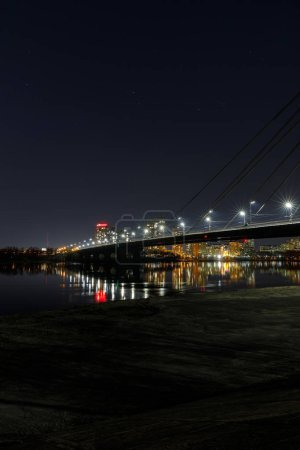 Photo for Cityscape with illuminated buildings, bridge and river at nigth - Royalty Free Image