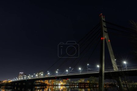 Photo for Dark cityscape with illuminated buildings and bridge - Royalty Free Image
