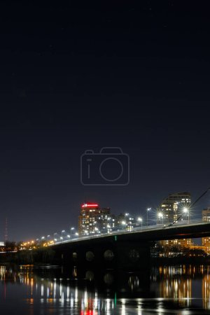 Photo for Dark cityscape with illuminated buildings, lights, bridge and river - Royalty Free Image