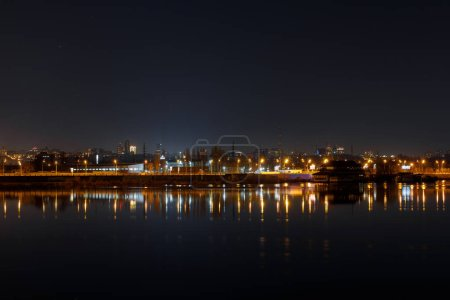 Photo for Dark cityscape with illuminated buildings and calm river at nigth - Royalty Free Image