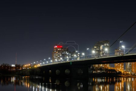 Photo for Cityscape with illuminated bridge above river at night - Royalty Free Image