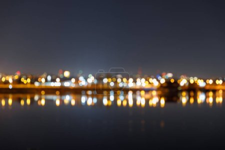 Photo for Dark cityscape with defocused illuminated buildings and river - Royalty Free Image