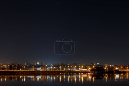 Photo for Dark cityscape with buildings, lights and river at night - Royalty Free Image
