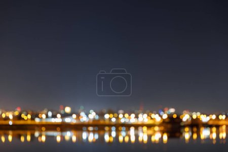 Photo for Dark cityscape with buildings, bokeh lights and river at night - Royalty Free Image
