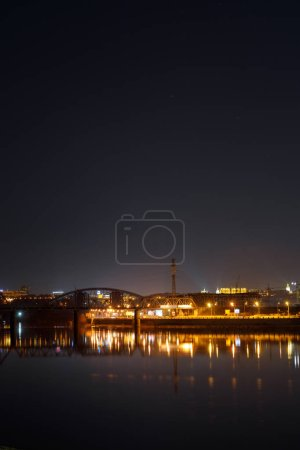 Photo for Dark cityscape with buildings, lights, river and night sky - Royalty Free Image