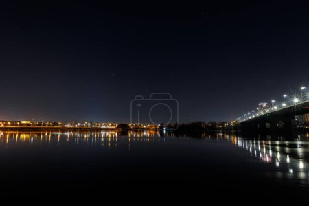 Photo for Dark cityscape with buildings, bridge, lights, river and night sky - Royalty Free Image