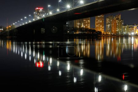 Photo for Dark cityscape with illuminated bridge and reflection on river at night - Royalty Free Image