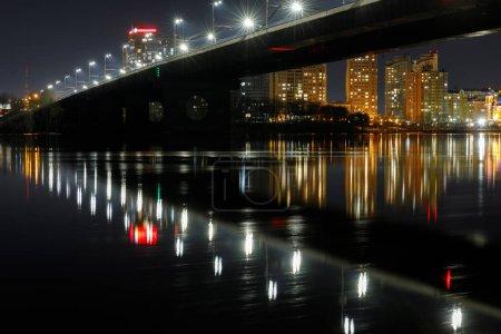 dark cityscape with illuminated bridge and reflection on river at night