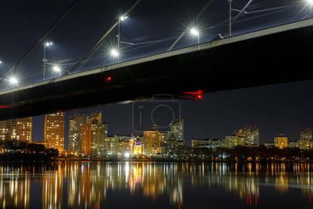 Photo for Dark cityscape with bridge, reflection on river and illuminated houses at night - Royalty Free Image