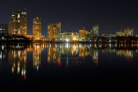 Photo for Dark cityscape with illuminated buildings with reflection on water at night - Royalty Free Image