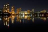 """Постер, картина, фотообои """"Темный городской пейзаж с подсветкой зданий с отражением на воде в ночное время"""""""