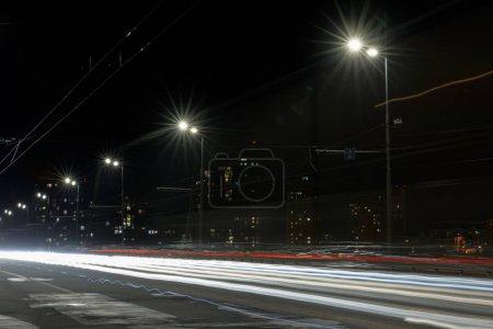 Photo pour Longue exposition des lumières sur la route la nuit près des bâtiments éclairés - image libre de droit