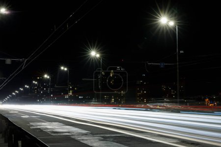 Photo for Long exposure of lights on road at nighttime near buildings - Royalty Free Image