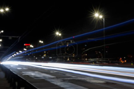 long exposure of lights on road at nighttime near illuminated buildings