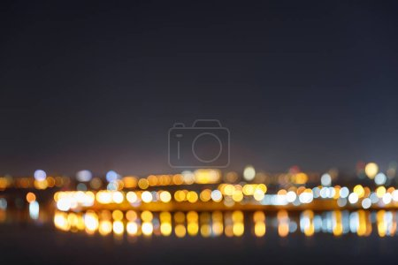 dark cityscape with illuminated blurred buildings, bridge and river