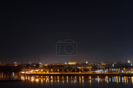 Photo for Tranquil cityscape with illuminated buildings and reflection on river at night - Royalty Free Image