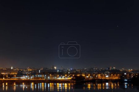 Photo for Dark and tranquil cityscape with illuminated buildings and reflection on river at night - Royalty Free Image
