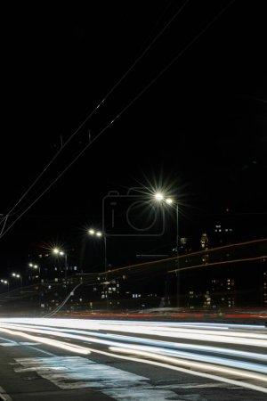 Photo pour Longue exposition des lumières sur la route la nuit ville animée - image libre de droit