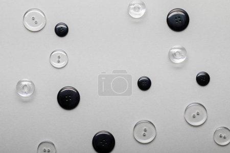 Foto de Vista superior de los botones de ropa transparentes y negros aislados en gris - Imagen libre de derechos