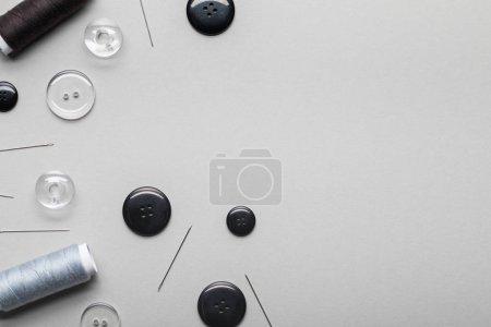 Photo pour Vue de dessus des boutons d'habillement, aiguilles et bobines de fil d'isolement sur le gris avec l'espace de copie - image libre de droit