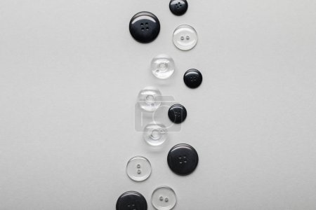 Foto de Vista superior de los botones de ropa negros y transparentes dispuestos aislados en gris con espacio de copia - Imagen libre de derechos