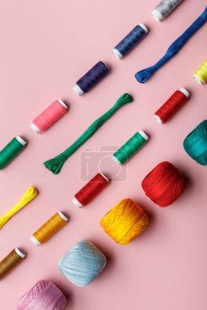 Photo pour Vue de dessus des boules colorées de fil à tricoter, fils de broderie et bobines de fil sur le rose - image libre de droit