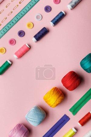 Photo pour Vue de dessus des boules, fils et fournitures de couture de tricot isolés sur rose avec espace de copie - image libre de droit
