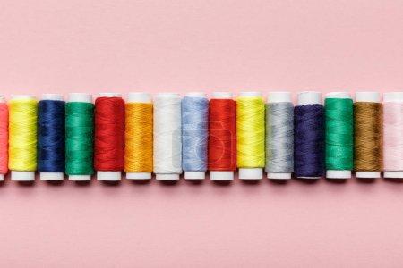 Foto de Vista superior de coloridas bobinas de hilo en fila en rosa - Imagen libre de derechos