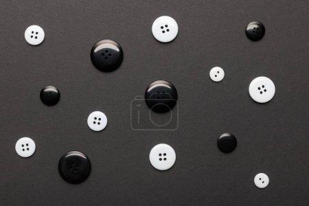 Foto de Vista superior de los botones de ropa monocromo aislados en negro - Imagen libre de derechos