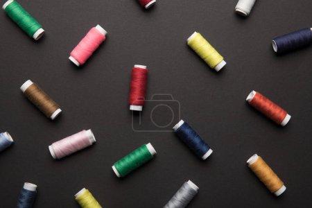 Photo pour Vue de dessus des bobines de fil colorées dispersées isolées sur le noir - image libre de droit
