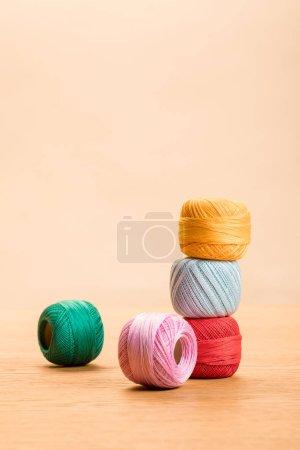 Photo pour Boules de fil de coton coloré à tricoter sur table en bois d'isolement sur le beige avec l'espace de copie - image libre de droit